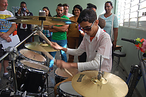 A student tries out a new drum kit donated by sponsored cyclists