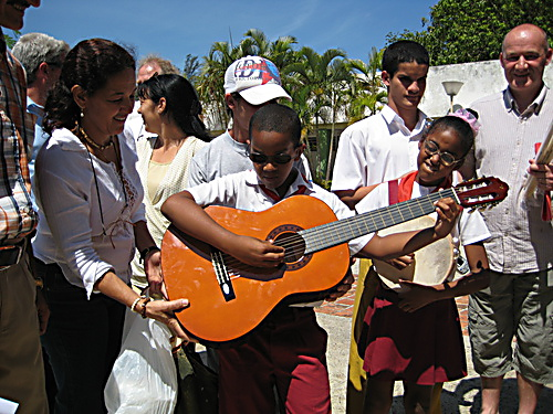 Handing over a guitar to one of the students